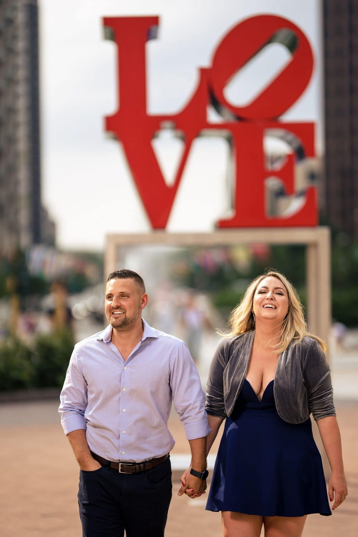 Couple walking through love park holding hands Philadelphia Engagement Shot By John Ryan