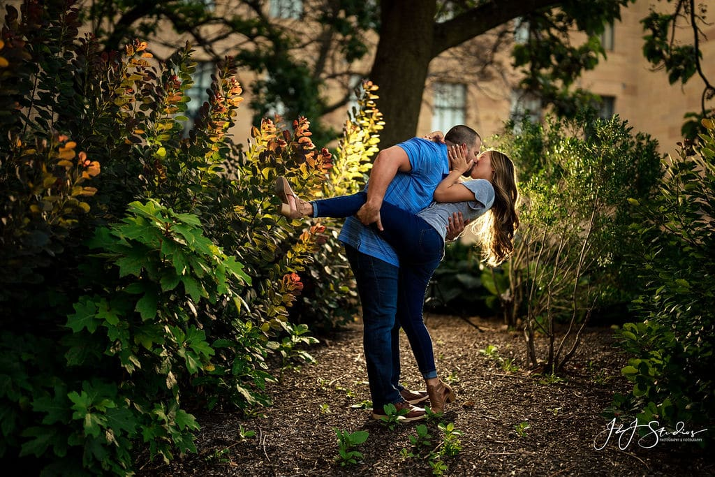 Jackie and Rich embracing in the woods Philadelphia Museum of Art and Fairmount Waterworks Engagement Shot By John Ryan