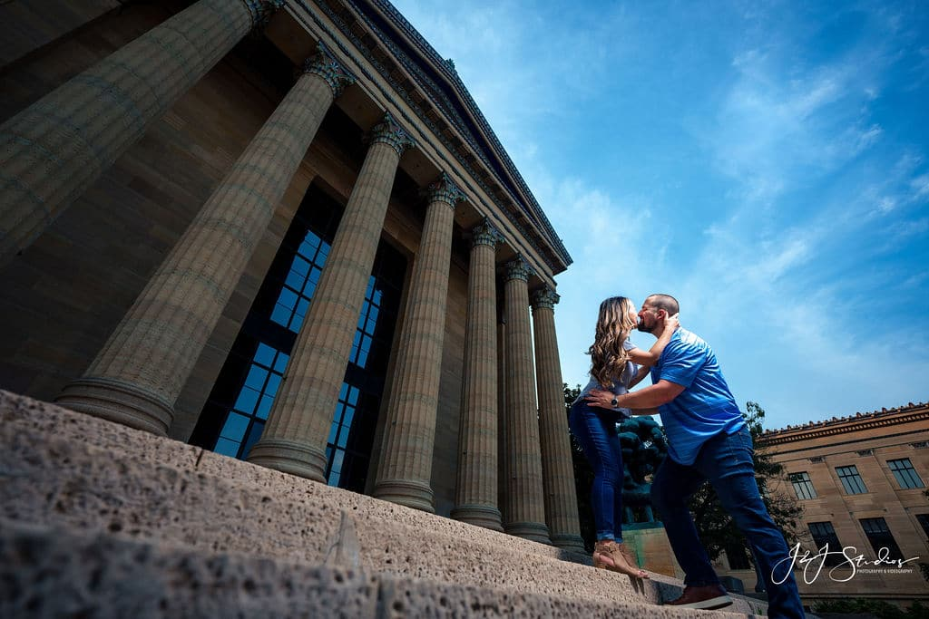 Couple running of the steps of the Philly Museum of Art Philadelphia Museum of Art and Fairmount Waterworks Engagement Shot By John Ryan