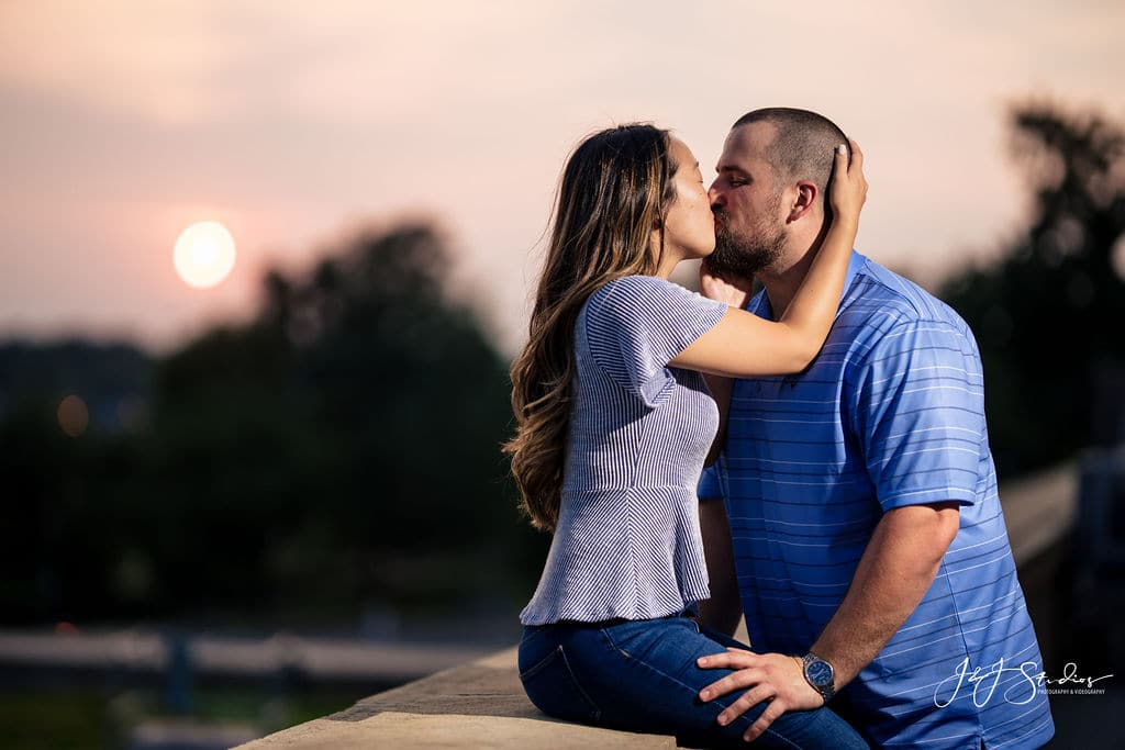 Couple kissing under the sunset in Philly Philadelphia Museum of Art and Fairmount Waterworks Engagement Shot By John Ryan