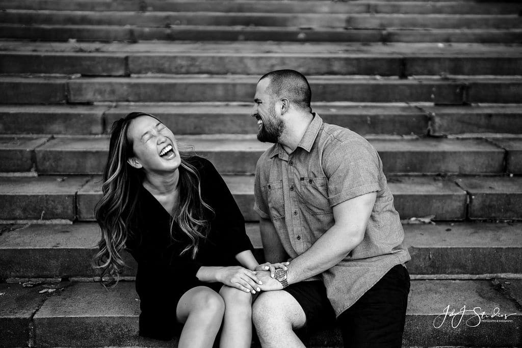 Couple siting on the steps of the Philly Museum Philadelphia Museum of Art and Fairmount Waterworks Engagement Shot By John Ryan