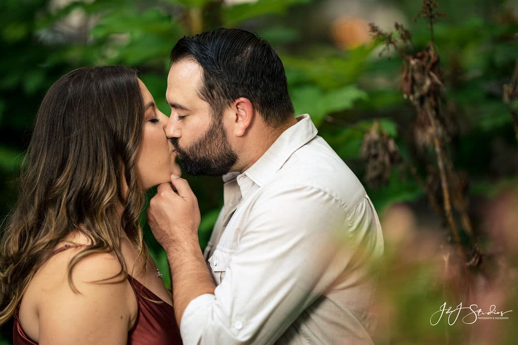 Sweet kiss between engaged couple Rittenhouse Square and Addison Street Engagement Shot By John Ryan