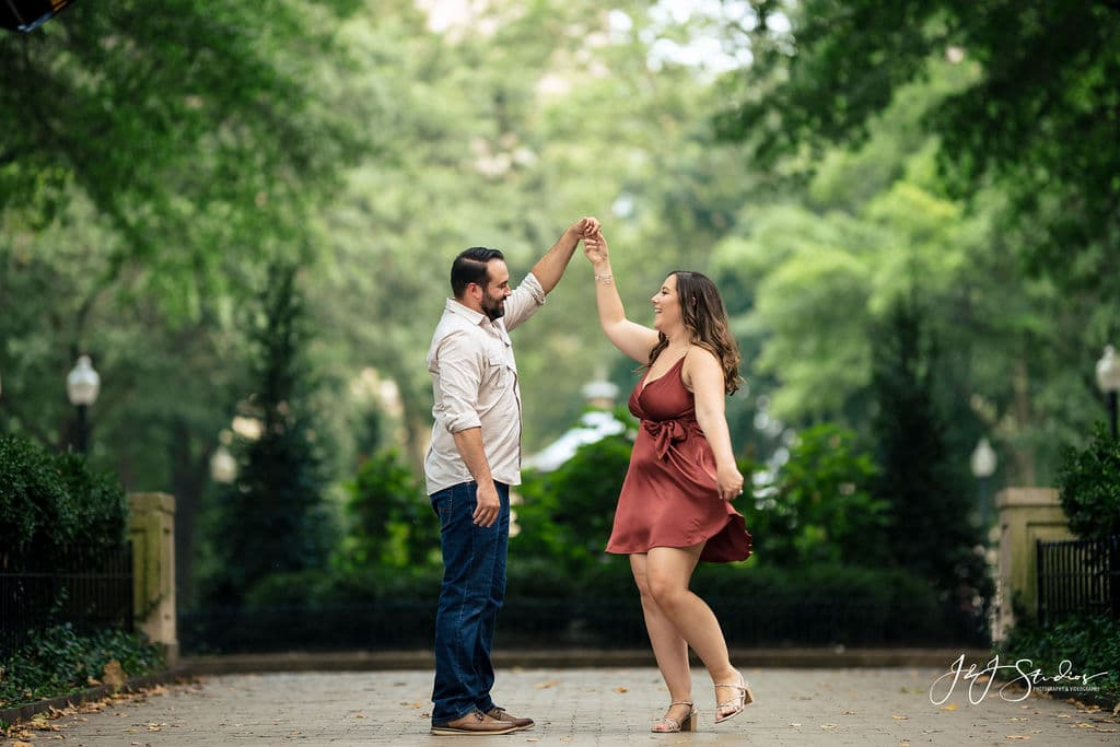 Engaged couple dancing near the trees in the park Rittenhouse Square and Addison Street Engagement Shot By John Ryan