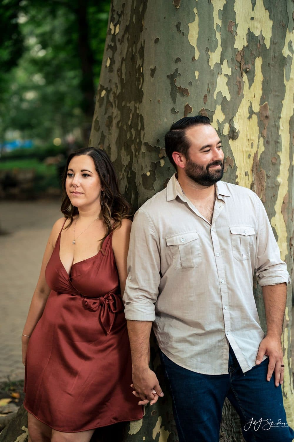 Sara and James against tree bark in the park Rittenhouse Square and Addison Street Engagement Shot By John Ryan