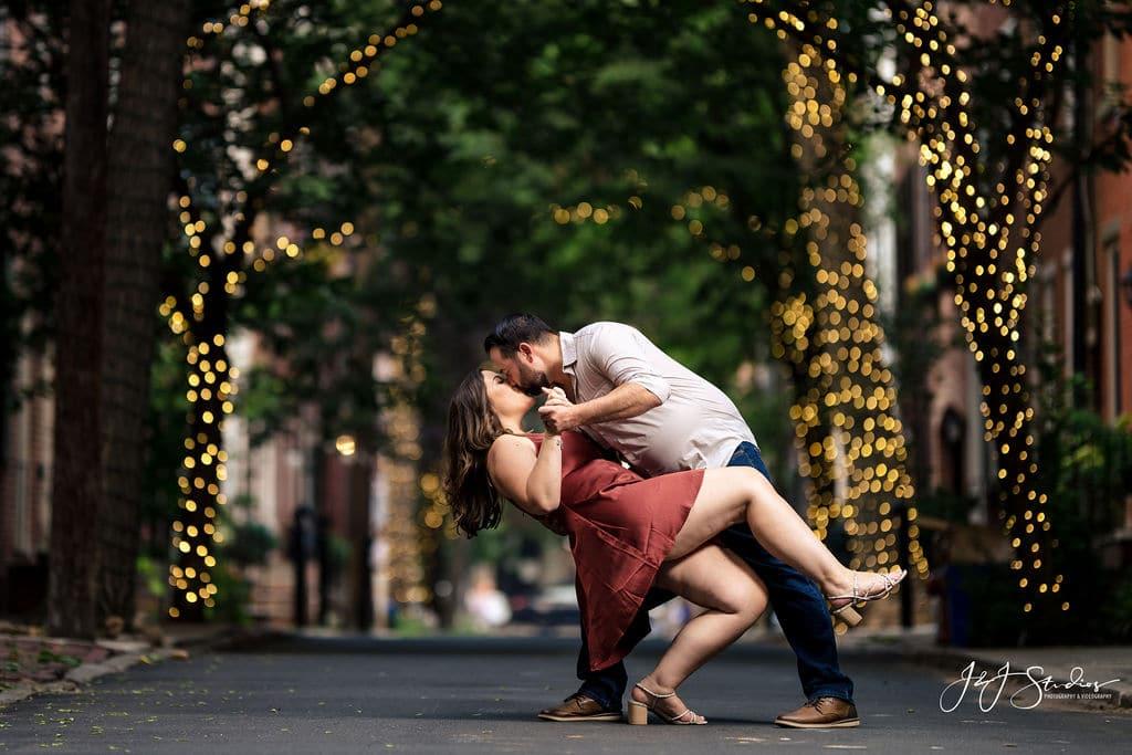 Romantic kiss under Addison Street lights Rittenhouse Square and Addison Street Engagement Shot By John Ryan