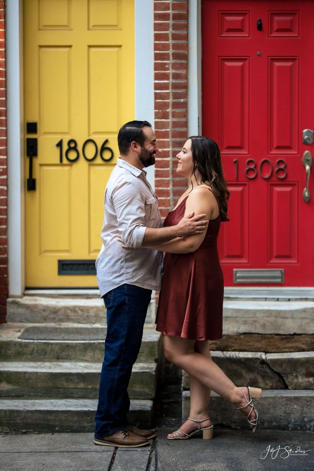 Sara and James near red and yellow door Rittenhouse Square and Addison Street Engagement Shot By John Ryan