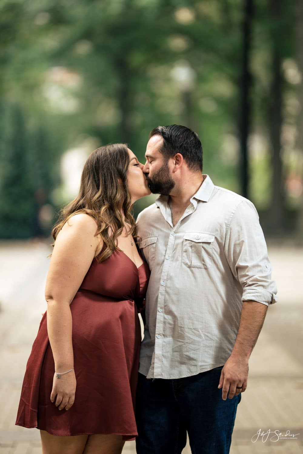 Engaged couple sharing a kiss at the park Rittenhouse Square and Addison Street Engagement Shot By John Ryan
