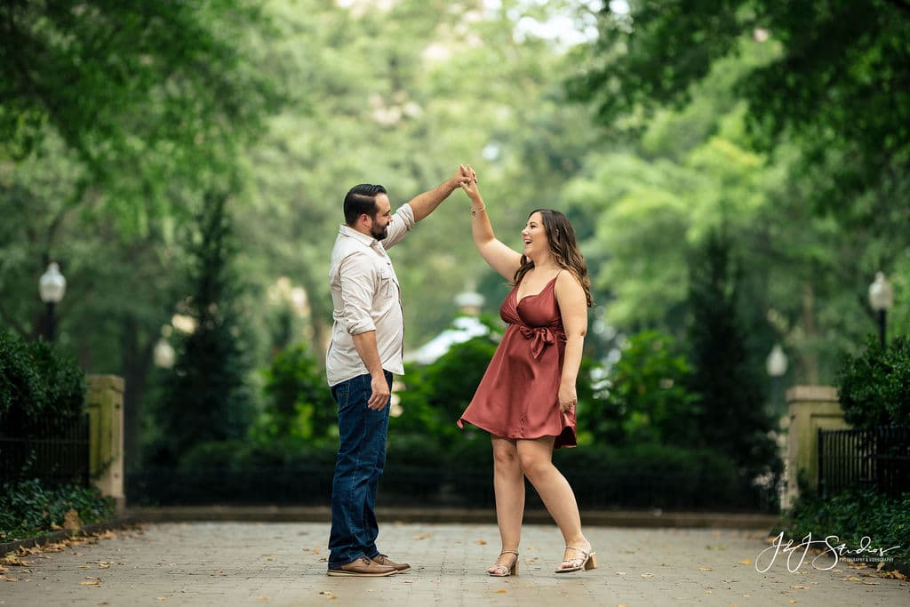 James twirling Sara at the park Rittenhouse Square and Addison Street Engagement Shot By John Ryan