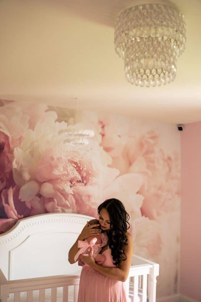 mom and daughter under chandelier in nursery