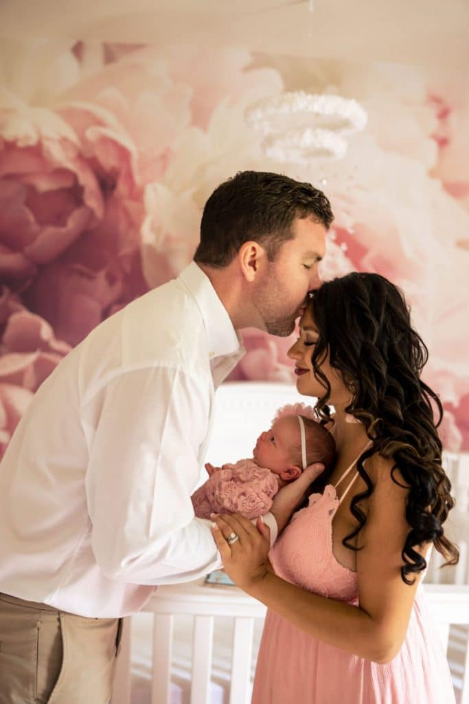 dad kissing mom's head over baby girl