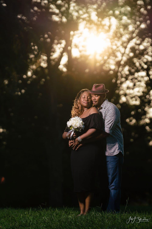 Couple embracing during sun down Curtis Arboretum Engagement Shot By John Ryan
