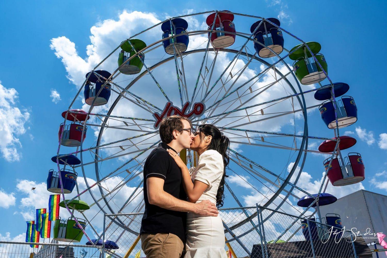 Couple in front of a ferris wheel by J&J Studios