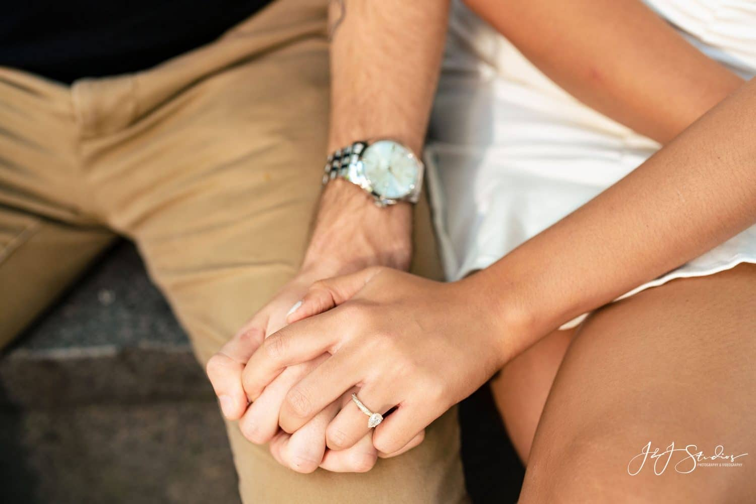 Engaged couple holding hands by J&J Studios