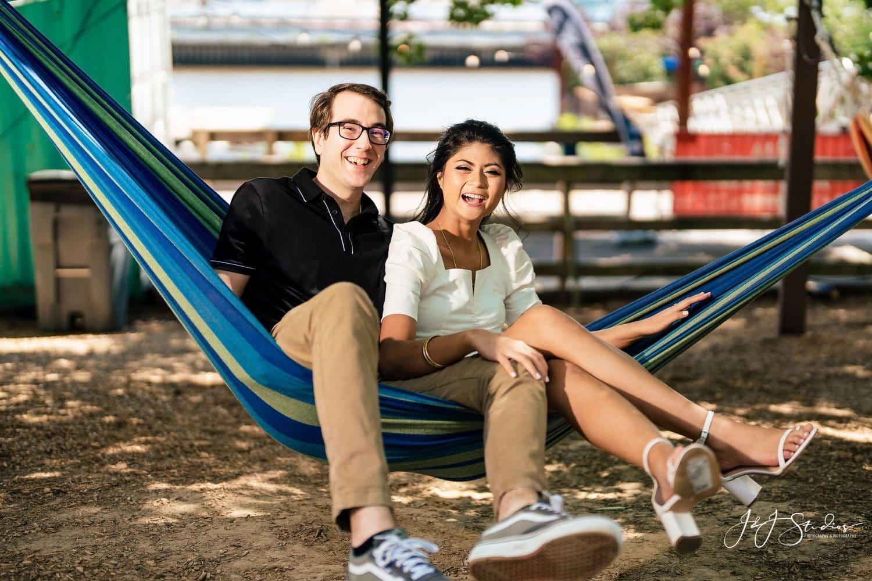 Couple sitting in a hammock by J&J Studios