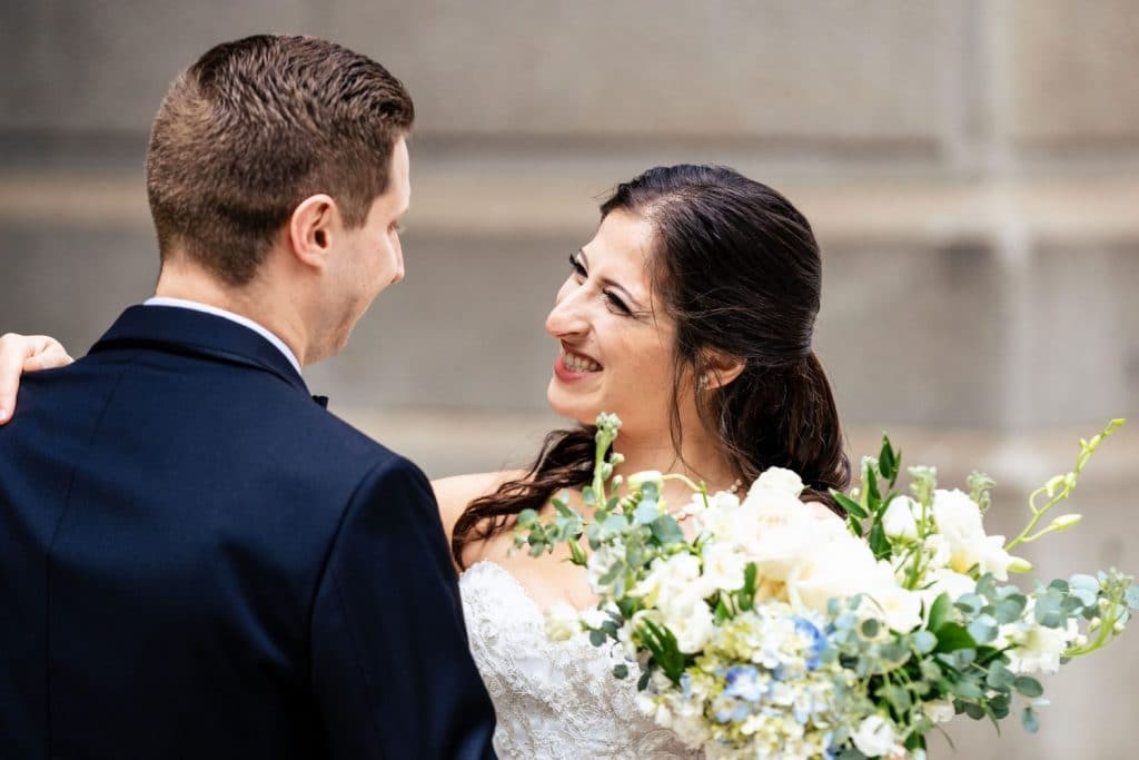 bride smiling at groom during first look wedding day
