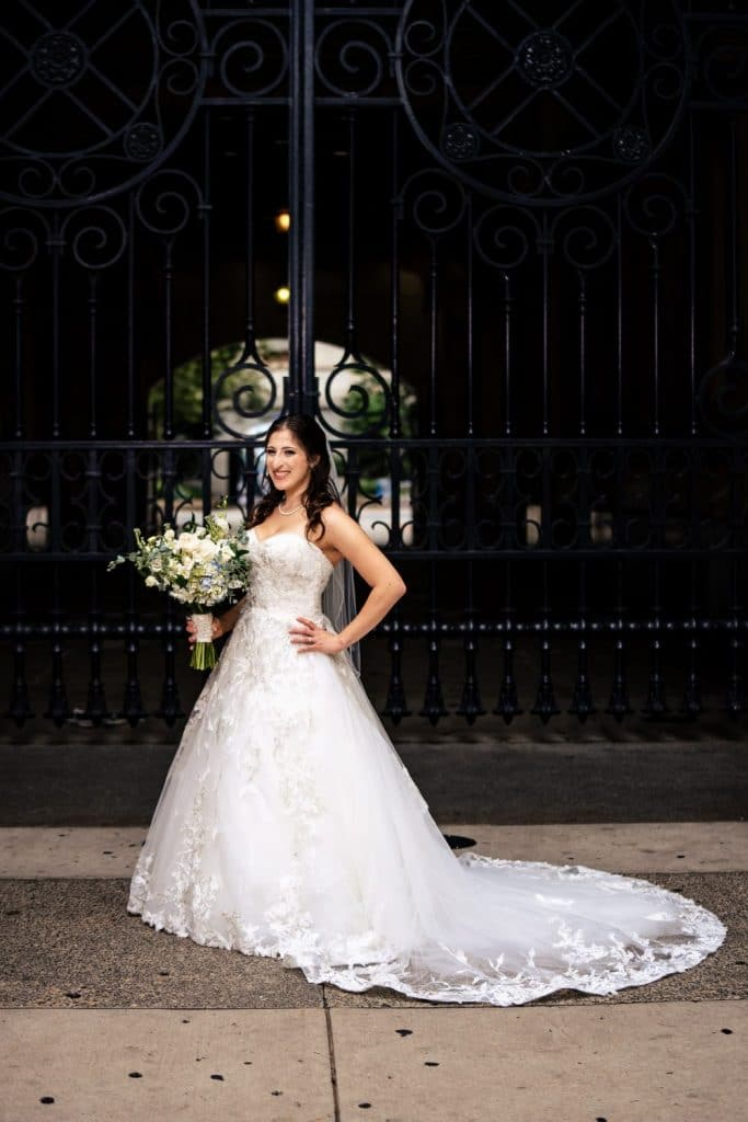 bride posing in wedding dress in front of iron gate
