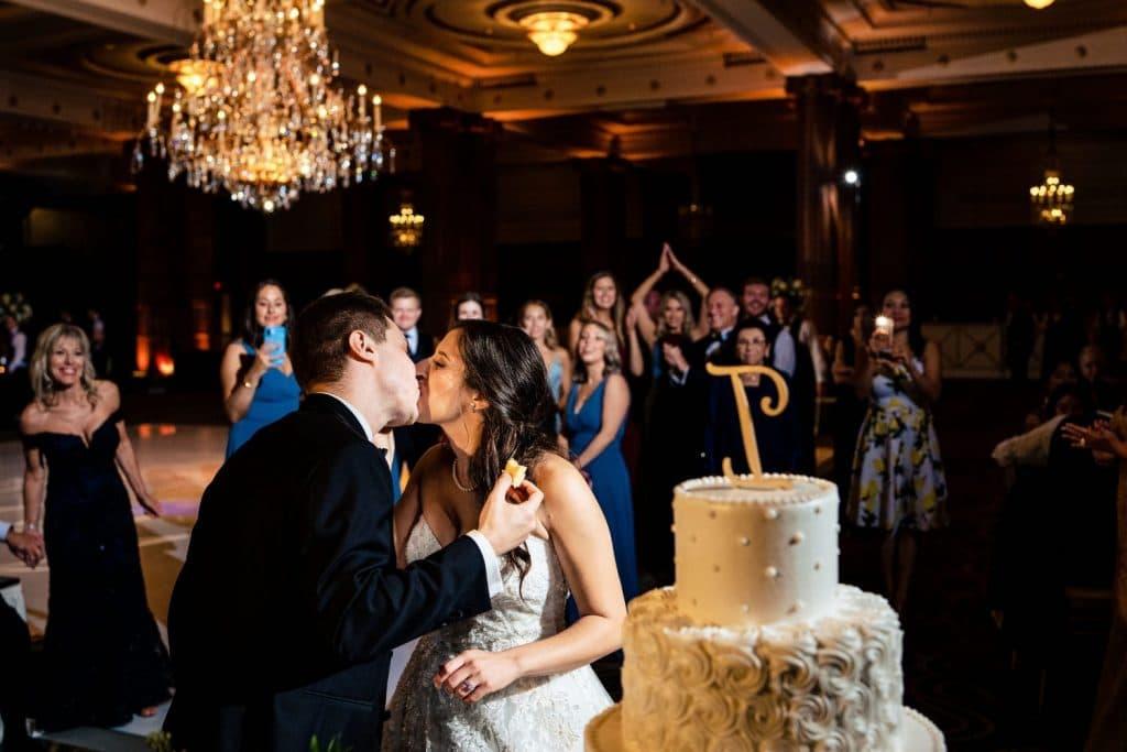 crystal tea room wedding bride and groom kiss after feeding each other cake