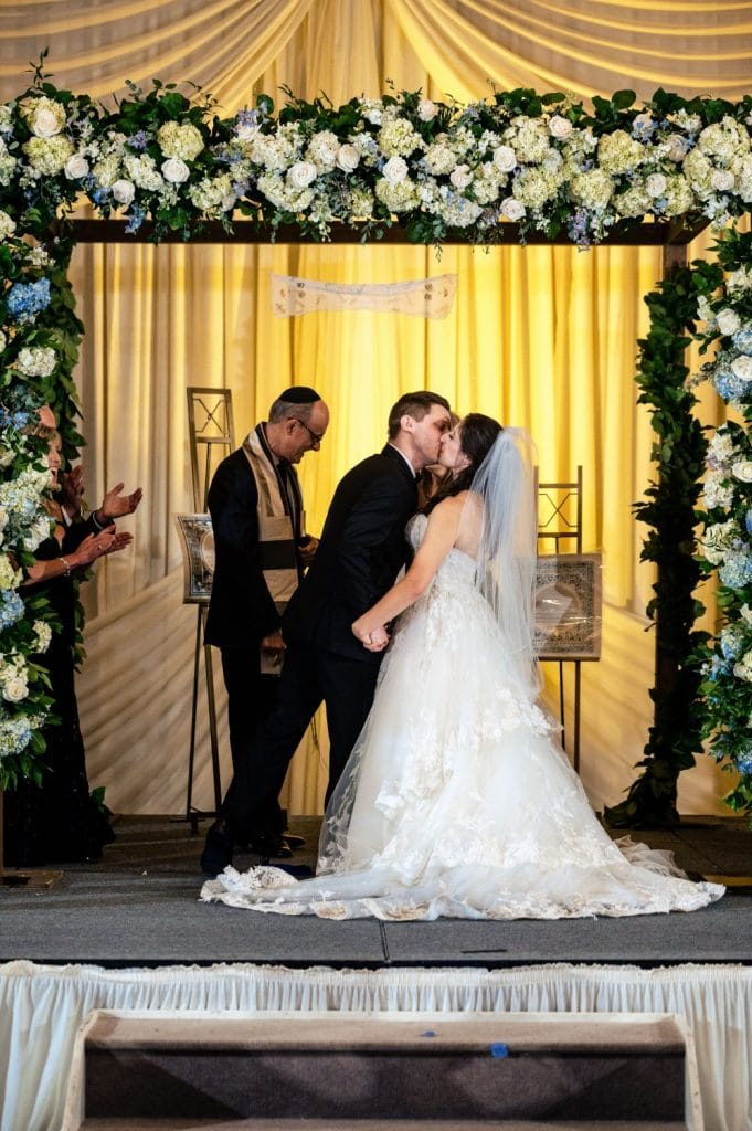 bride and groom first kiss wedding ceremony chuppah