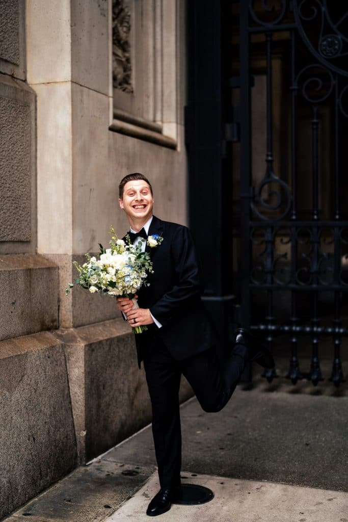 groom posing with bridal bouquet goofy