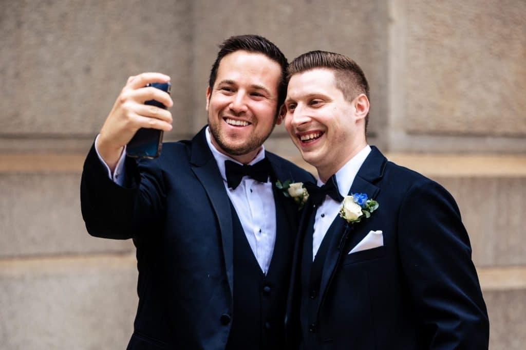 groom taking selfie with groomsman
