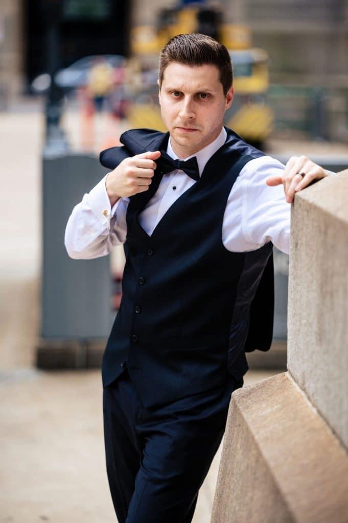 groom posing with jacket over shoulder