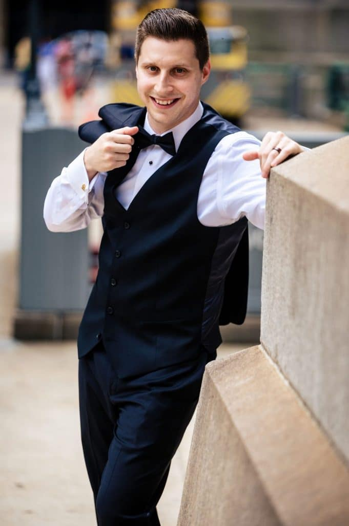 groom posing on city sidewalk