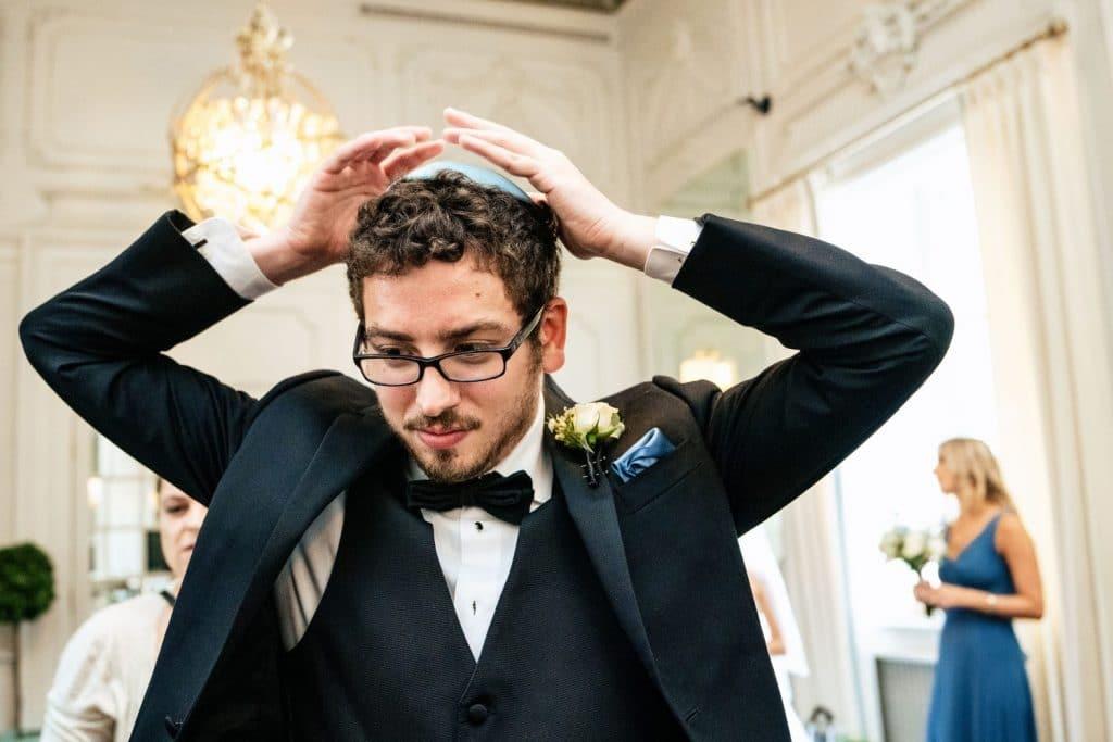groomsman putting on yarmulke wedding