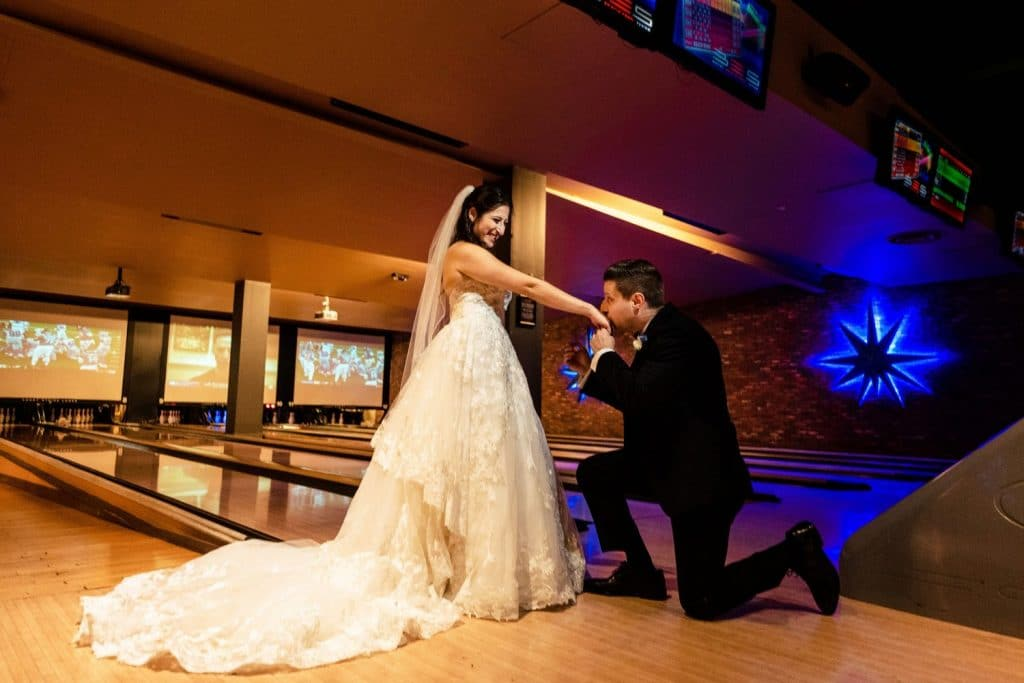 bowling alley wedding lucky strike philadelphia pa groom kneeling to kiss bride hand